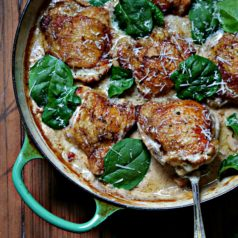 Chicken Thighs with Creamy Garlic Mushroom Sauce in green skillwt with spoon