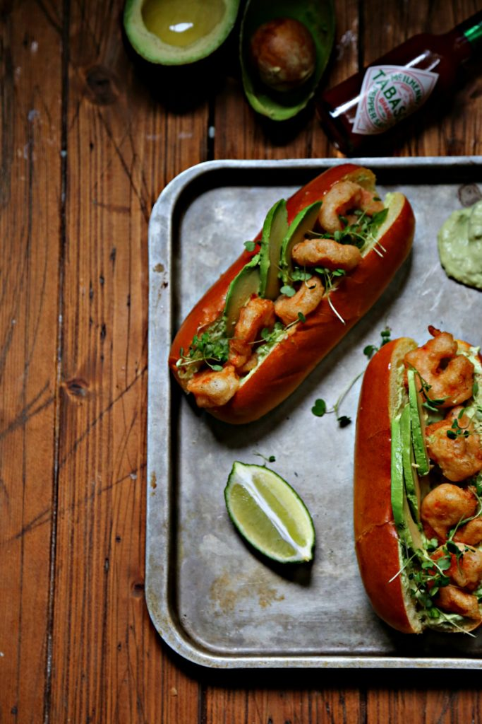 Spicy Shrimp Po Boy with Avocado Crema on baking sheet with lime and avocados and tabasco bottle to side