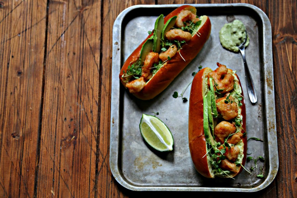Spicy Shrimp Po Boy with Avocado Crema on baking sheet with lime and spoon of avocado crema