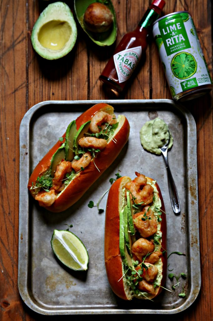 Spicy Shrimp Po Boy with Avocado Crema on baking sheet with lime, Tabasco bottle, avocads and lime a rita to side