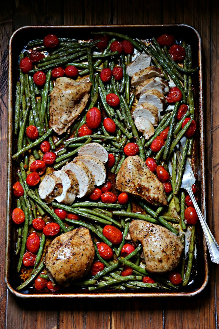 Chicken, Green Beans and Roma Tomatoes on a sheet pan. Serving fork under green beans.