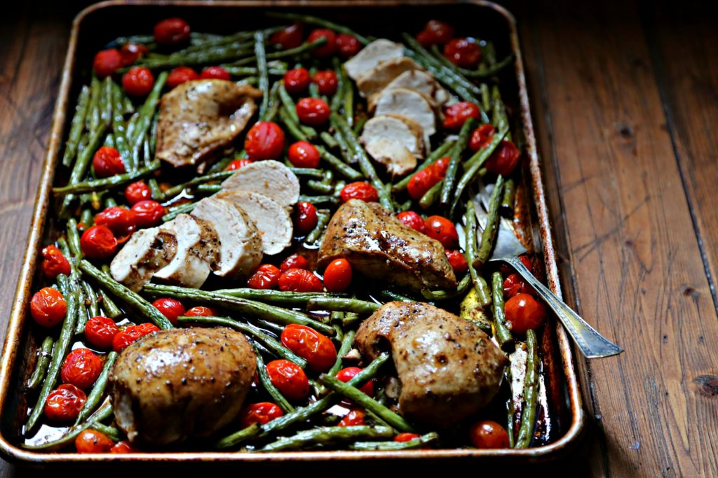 roasted chicken, green beans and tomatoes on a sheet pan with serving fork.