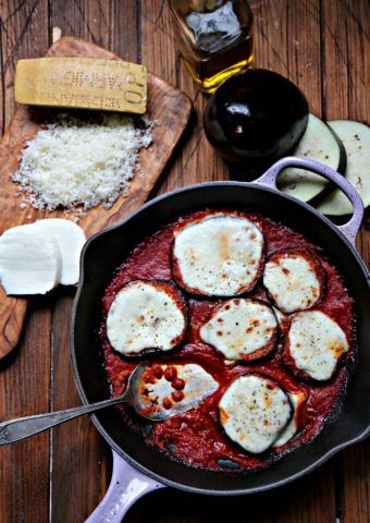 Skillet Eggplant Parmesan. Cutting board with Parmesan and mozzarella to side. Sliced eggplant behind.