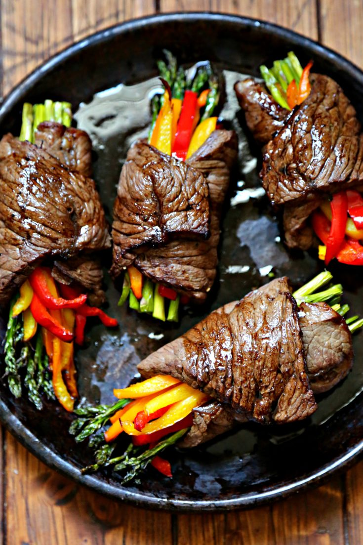 close up of 4 steak bundles filled with asparagus and colorful bell peppers.