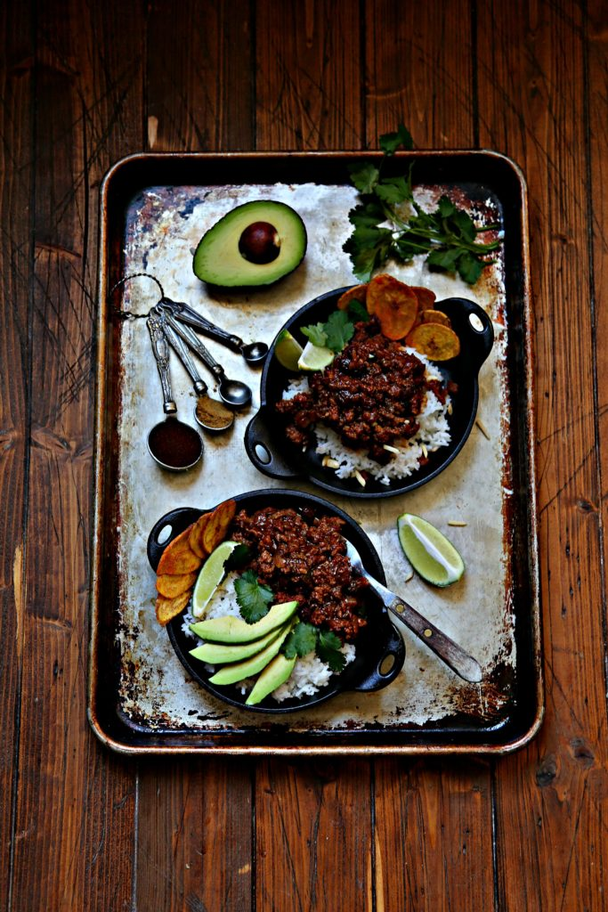 Sheet pan with 2 small skillets of picadillo. Sliced avocado, measuring spoons with spices, fresh cilantro scattered.