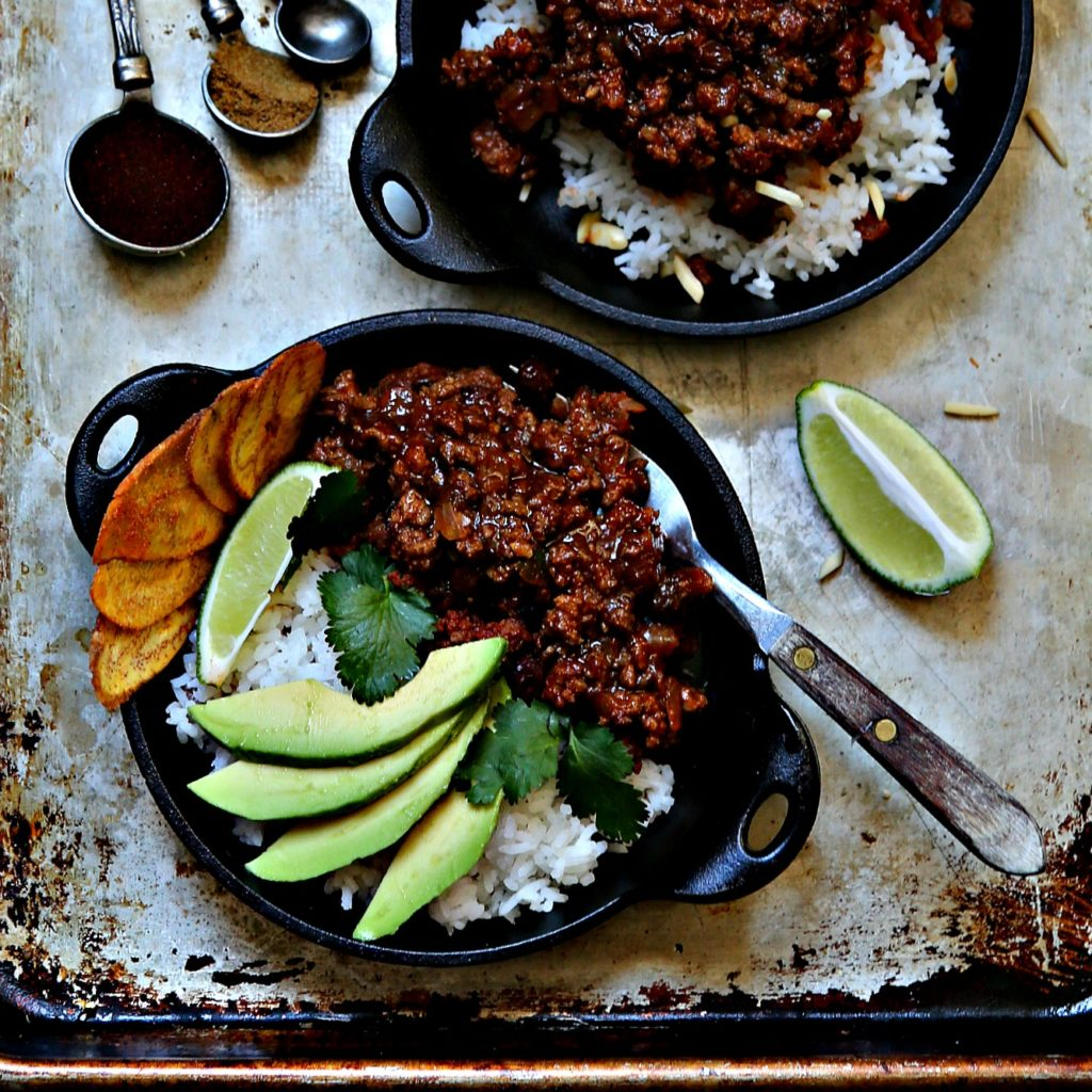 2 cast iron skillets of picadillo. Lime wedge, measuring spoons with spices to side.