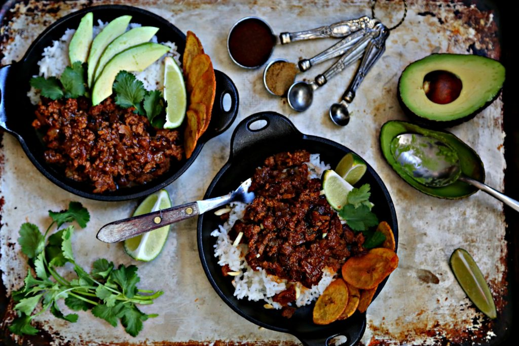 2 small cast iron skillets filled with rice, picadillo, cilantro, plaintain chips, avocados, lime slices. Measuring spoons with spices to side.