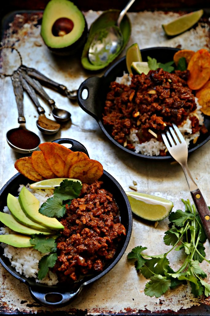 2 small cast iron skillets filled with rice, picadillo, avocado, cilantro, plaintain chips. Measuring spoons with spices behind.