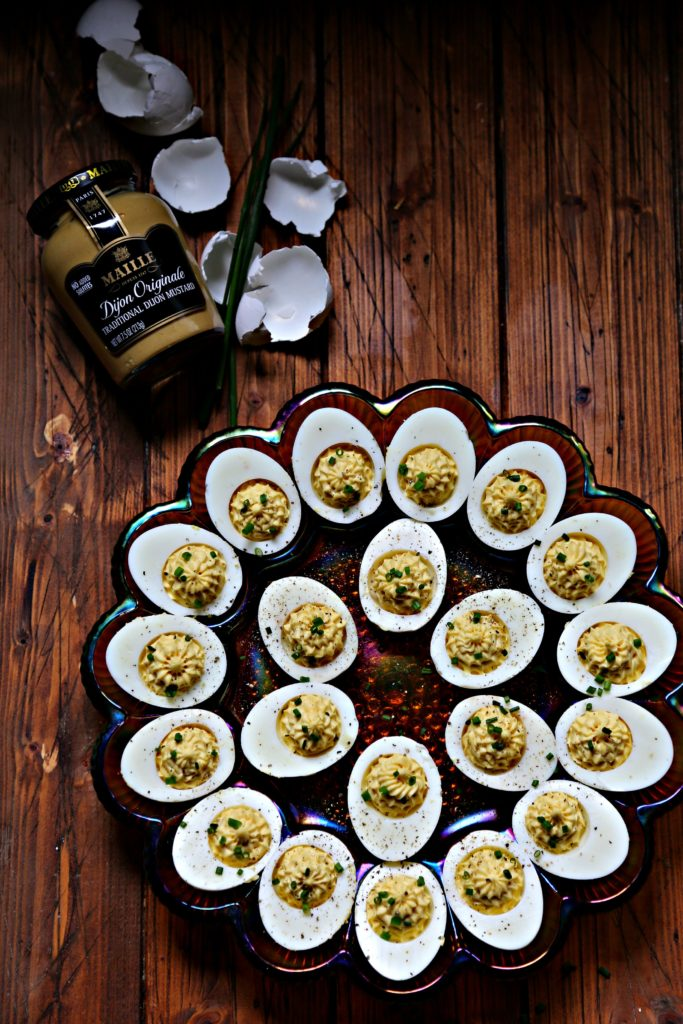 Deviled eggs on depression glass egg plate. Jar of Maille mustard to side along with egg shells and chives.