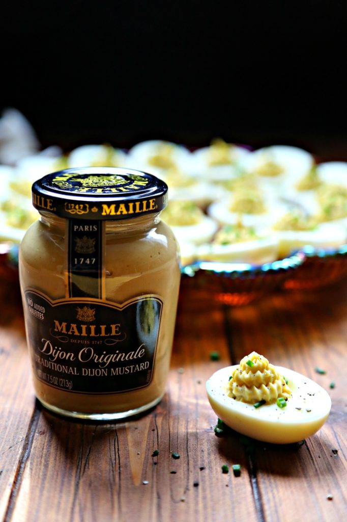 Jar of Maille mustard with one deviled egg beside. Tray of deviled eggs behind.