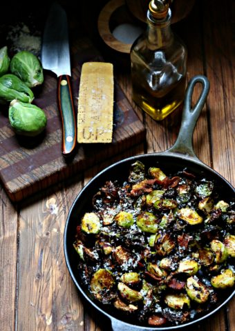 air fried Brussels Sprouts with Bacon in cast iron skillet. Cutting board with knife, brussels, parm wedge and bottle of olive oil behind.