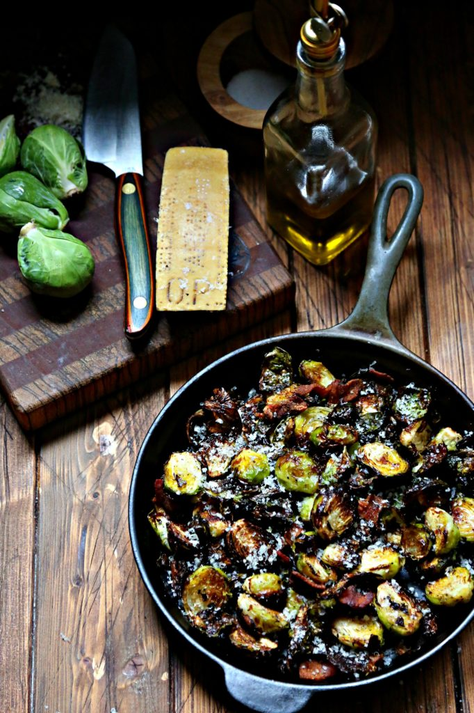 Brussels Sprouts with Bacon in cast iron skillet. Cutting board with knife, brussels, parm wedge and bottle of olive oil behind.