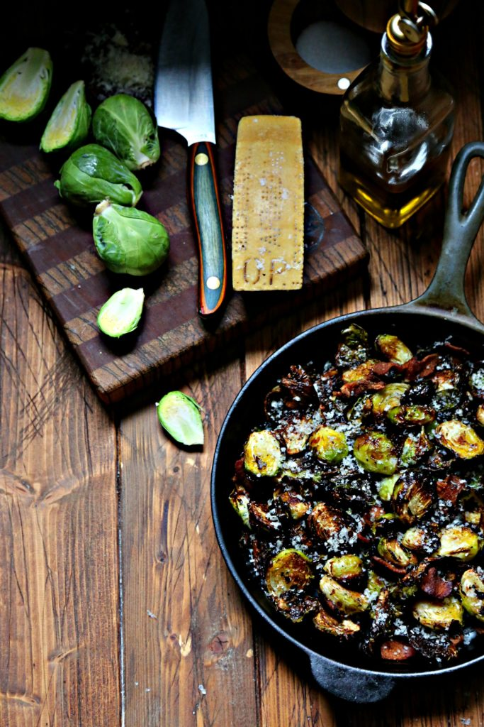 Brussels Sprouts with bacon in cast iron skillet. Cutting board with brussels, knife and parm wedge behind.