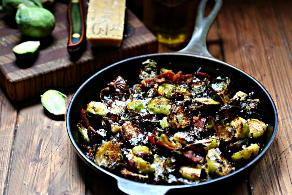 Brussels Sprouts with bacon in cast iron skillet. Cutting board with parm wedge, knife and brussels behind.