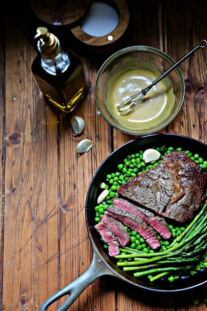 cast iron skillet with steak, spring peas and asparagus. Jar of olive oil, bowl of mustard vinaigrette with whisk to side.
