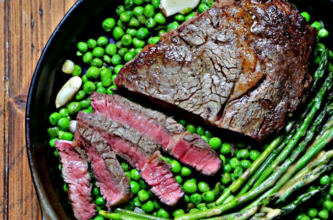Cast iron skillet with spring peas, asparagus and steak.
