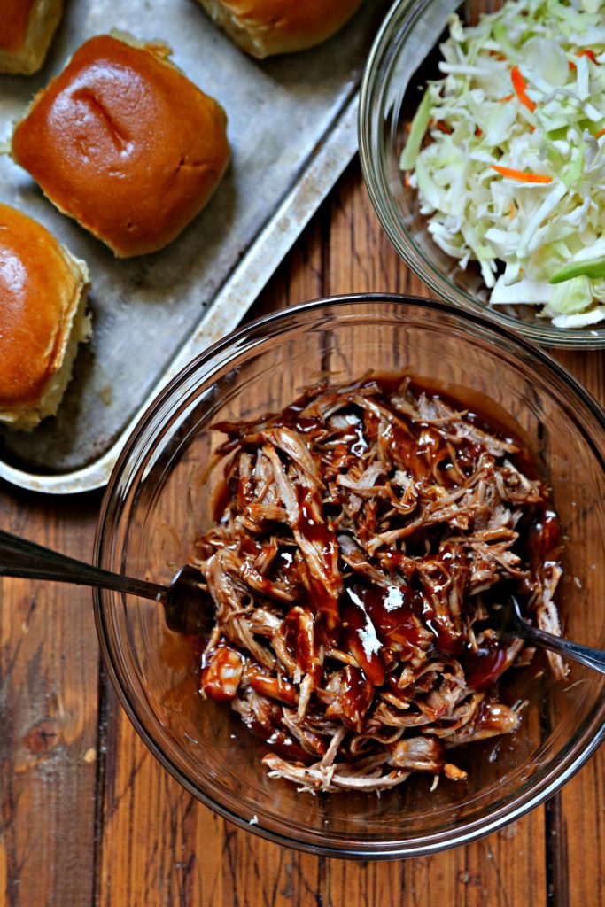 Bowl of bbq pulled pork with spoon. Bowl of coleslaw and baking sheet with buns behind.
