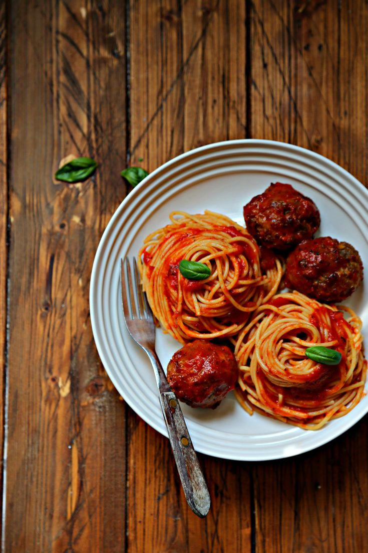 spaghetti and meatballs in white bowl with fork.