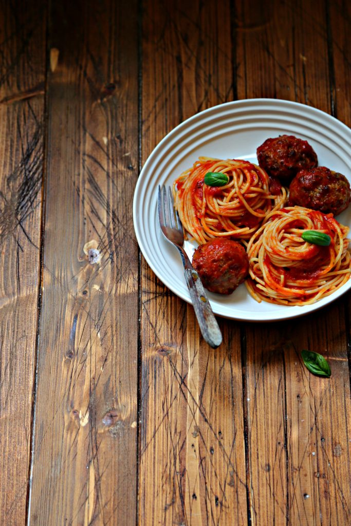 spaghetti and meatballs in white bowl with fork. Basil leaf in front.
