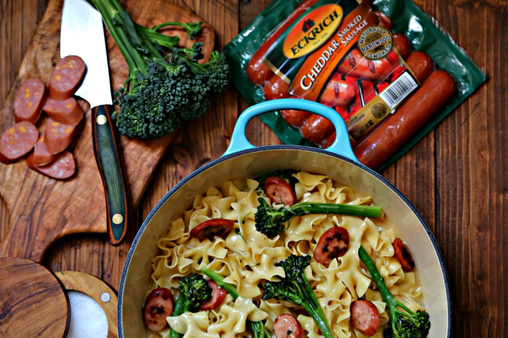 Sausage Pasta in Blue pot. Cutting board with knife, broccoli and package of smoked sausage behind.