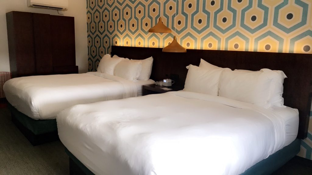 two beds in a hotel room with white comforters.