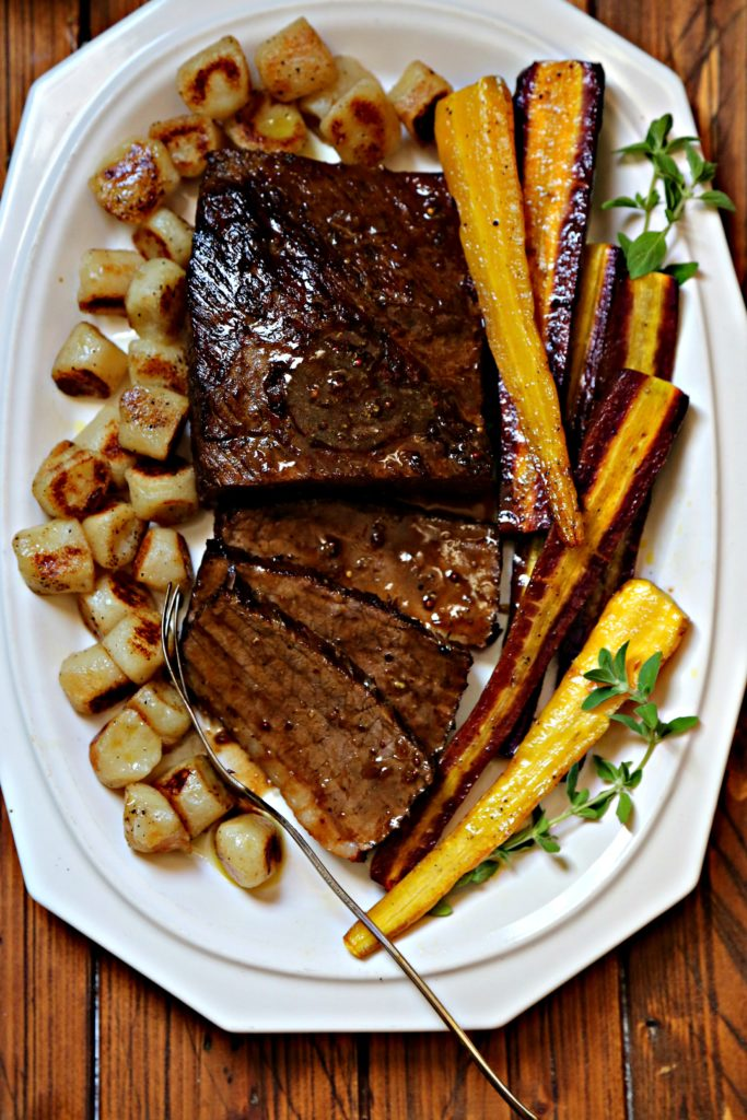 braised beef brisket on white platter with roasted rainbow carrots and cauliflower gnocchi.