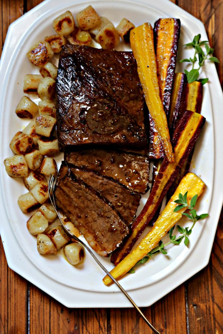 brisket on white platter with roasted rainbow carrots and cauliflower gnocchi.