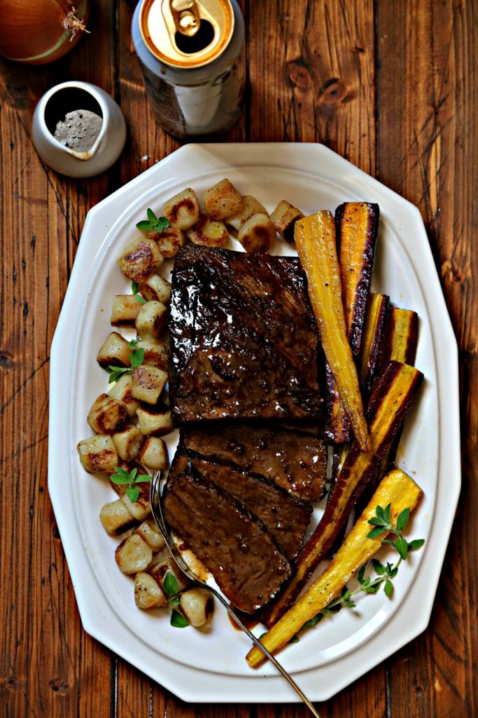 Brisket on white platter with gnocchi and carrots.