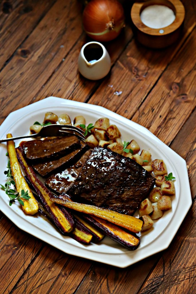 Braised Beef Brisket with cauliflower gnocchi and carrots on white platter with fork.