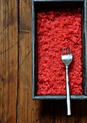 strawberry granita in metal loaf pan with fork.