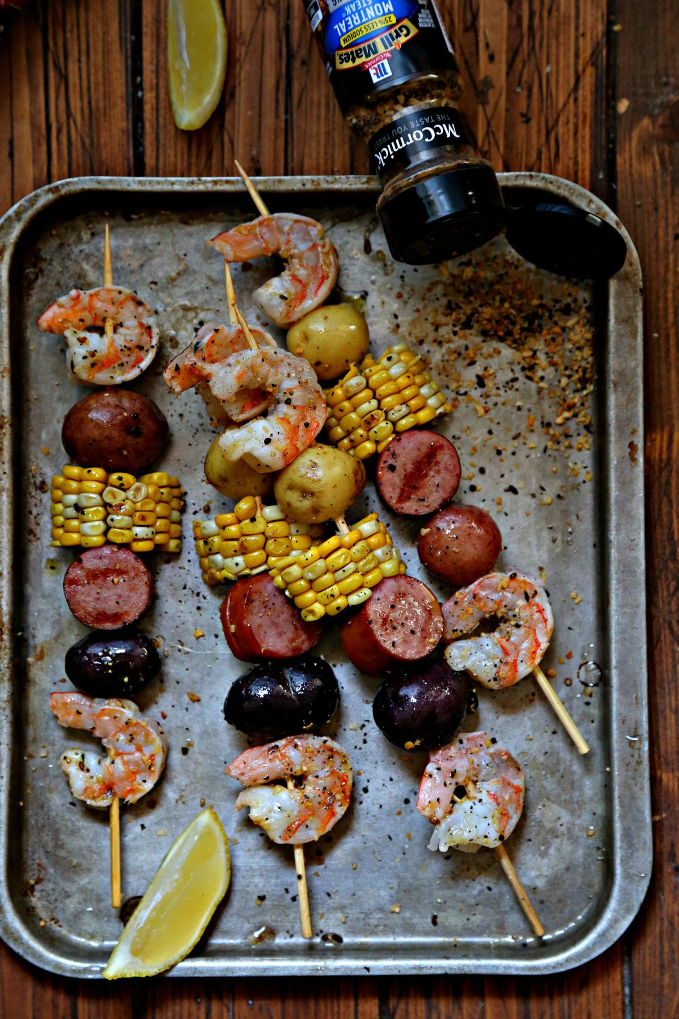 low country boil kebabs on baking sheet with spice jar.