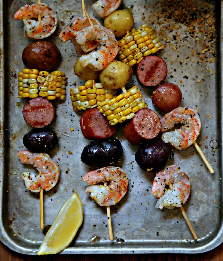 low country boil skewers on baking sheet.