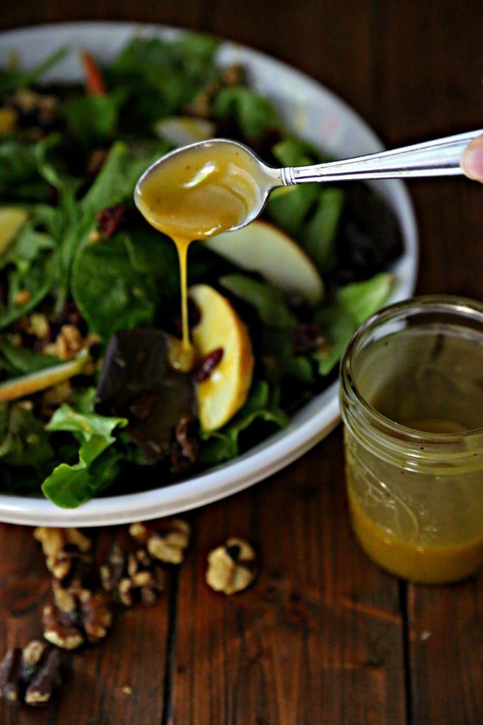 bowl of salad with spoon of honey mustard dressing drizzling on.