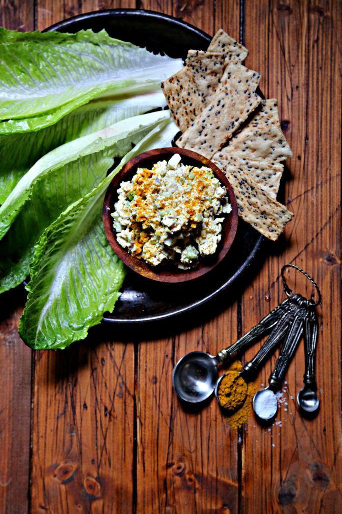 chicken salad in small wood bowl on plate surrounded with crackers and lettuce.