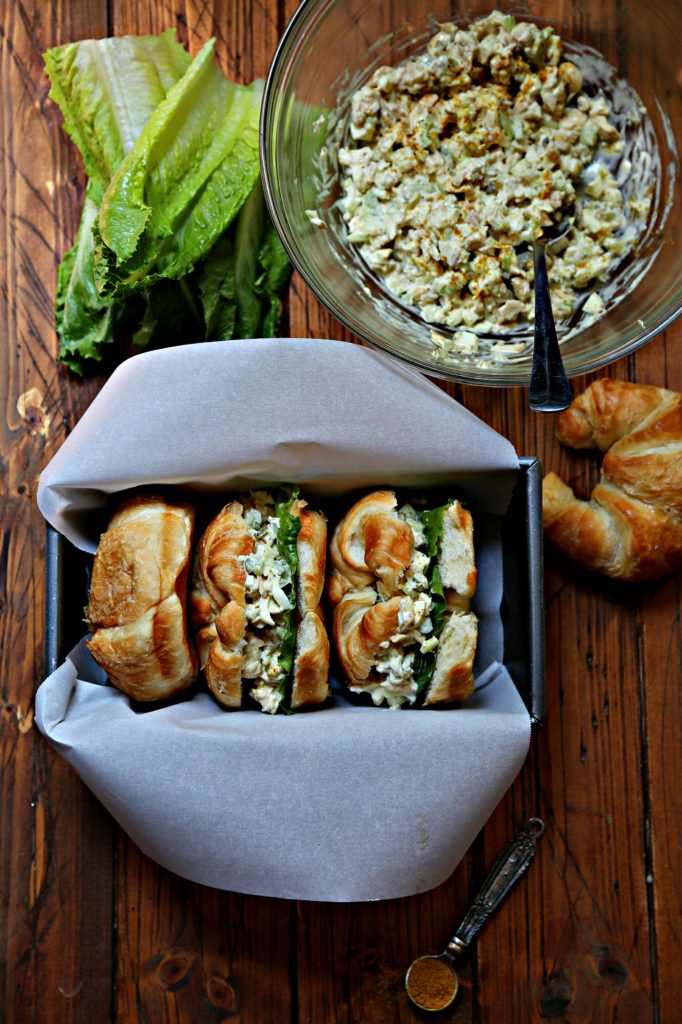Chicken Salad Sandwiches in loaf pan. Bowl of chicken salad and pieces of lettuce behind.
