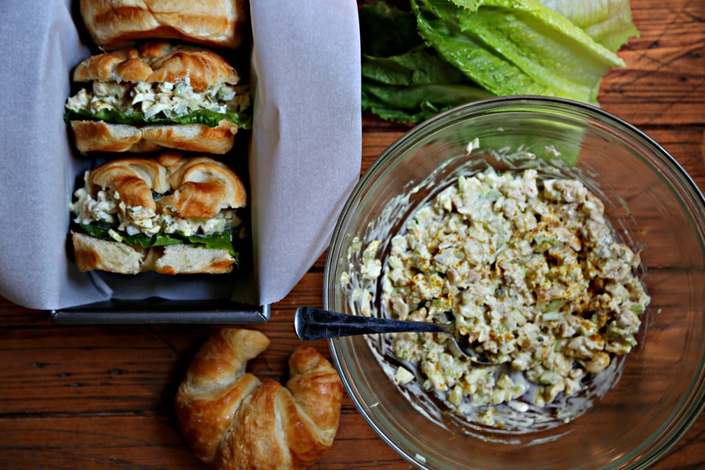Chicken Salad Sandwiches on croissants in loaf pan. Bowl of chicken salad to side.