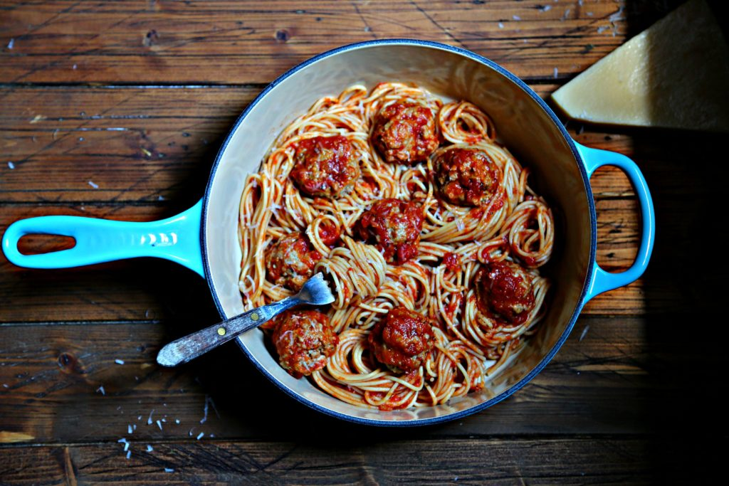 Spaghetti and Meatballs in blue pot. Cheese wedge to side.