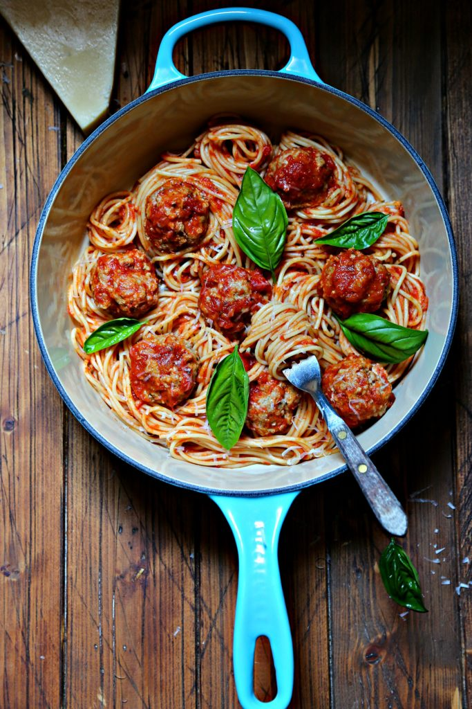 spaghetti and meatballs in blue pot with basil.