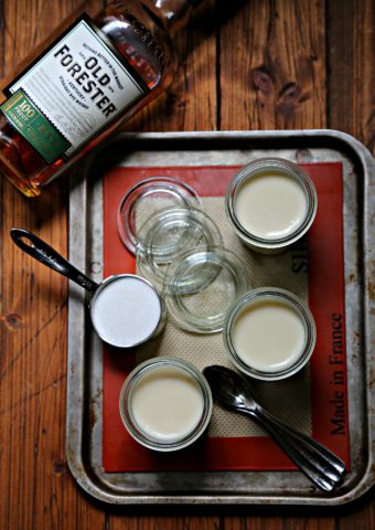 small glass jars filled with whiskey panna cotta on baking sheet with bottle of rye.
