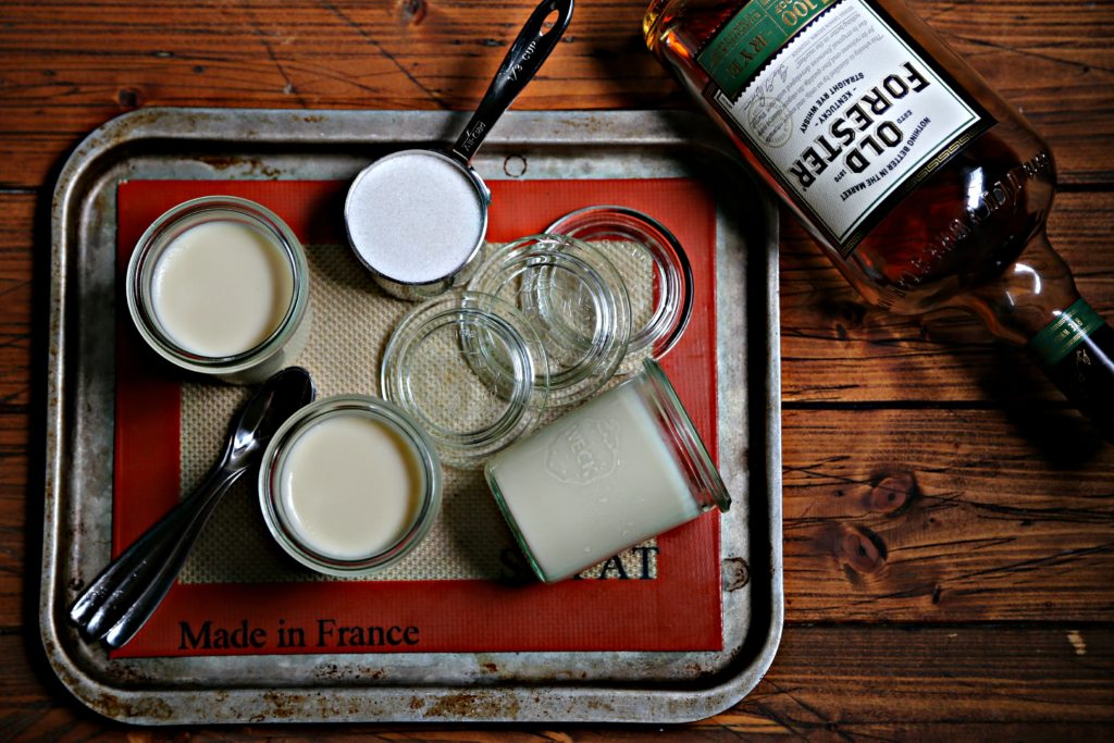 small glass jars of whiskey panna cotta on baking sheet with cup of sugar and bottle of rye.
