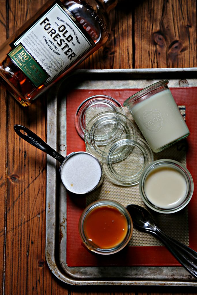 glass jars of whiskey panna cotta on baking sheet with bottle of rye.