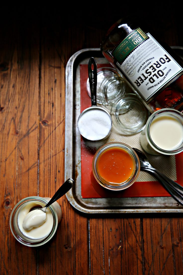 glass jars of panna cotta on baking sheet with bottle of rye.