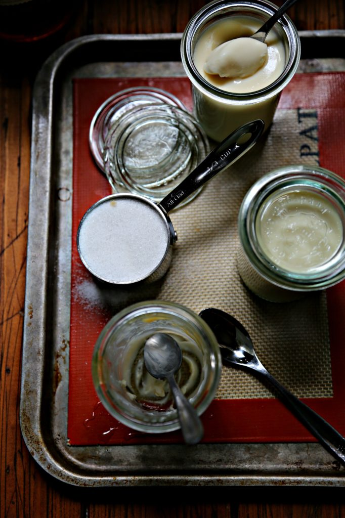 glass jars of whiskey panna cotta on baking sheet with cup of sugar.
