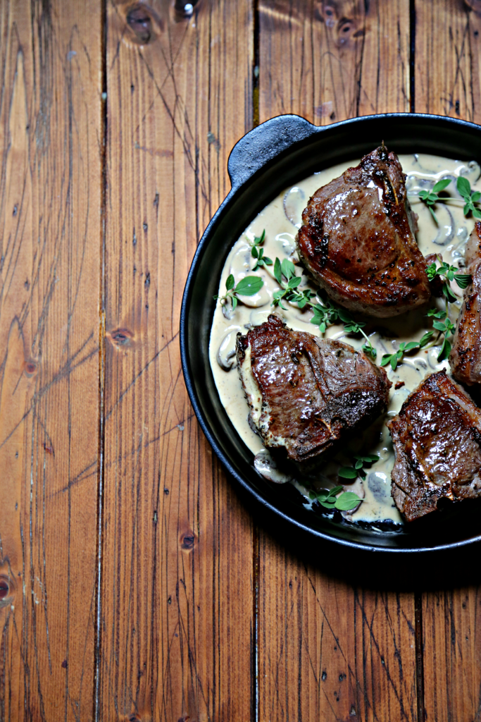 lamb chops in mustard sauce in cast iron skillet.