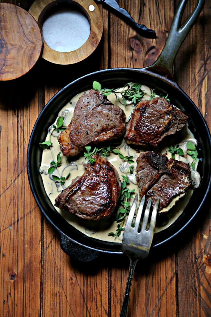 Lamb chops in mustard sauce in cast iron skillet with serving fork.