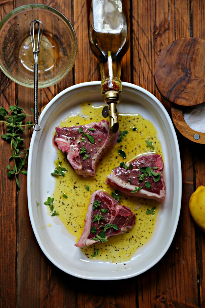lamb chops marinating in white dish with herbs.
