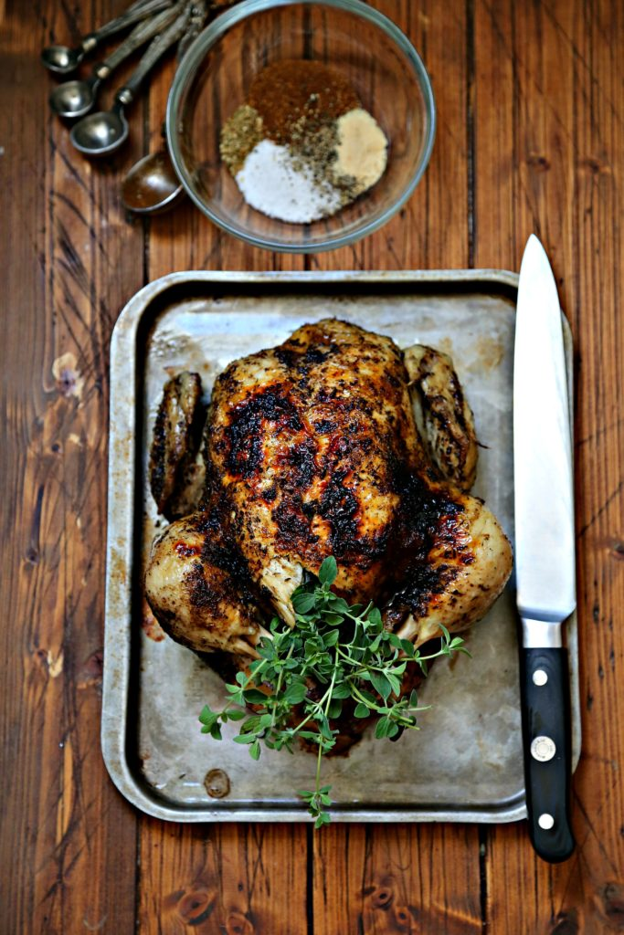 Roasted chicken on baking sheet with knife.