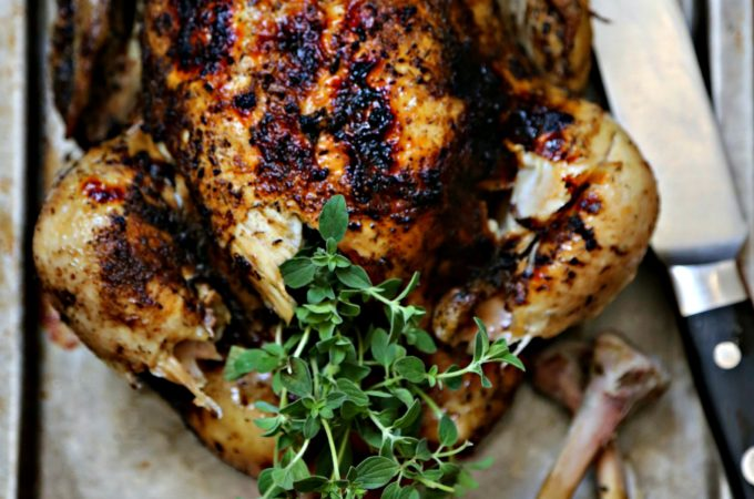 Whole roasted chicken on baking sheet with knife.
