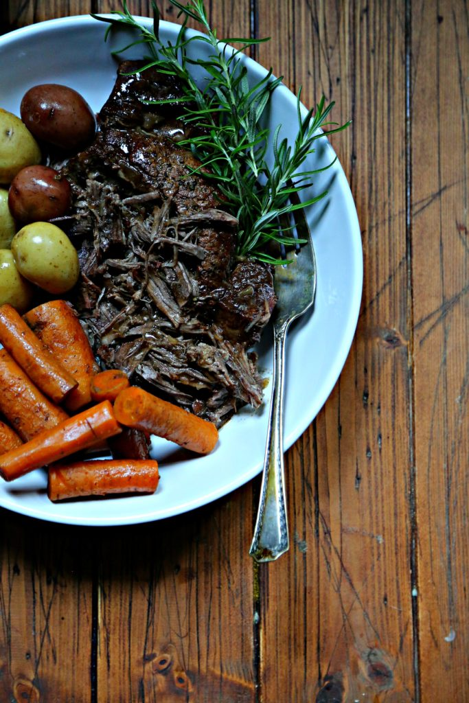 pot roast, carrots, potatoes in white bowl with serving fork.