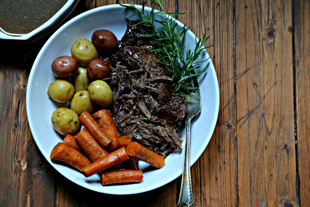 pot roast, carrots and potatoes in white bowl with serving fork.